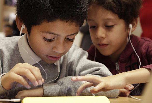 Jose Lucero, left, and Osiel Dominguez collaborate on a Star Wars game hosted on code.org at an Apple Store, Wednesday, Dec. 9, 2015 in New York. Third graders from PS 57 James Weldon Johnson School were invited to the store to participate in Computer Science Education Week. (AP Photo/Mark Lennihan)