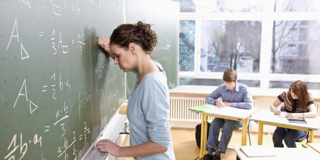 Teacher leaning against black board